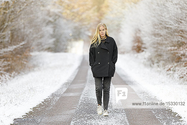 Young woman walking on snowy road