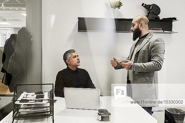 Men talking in office Men talking in office