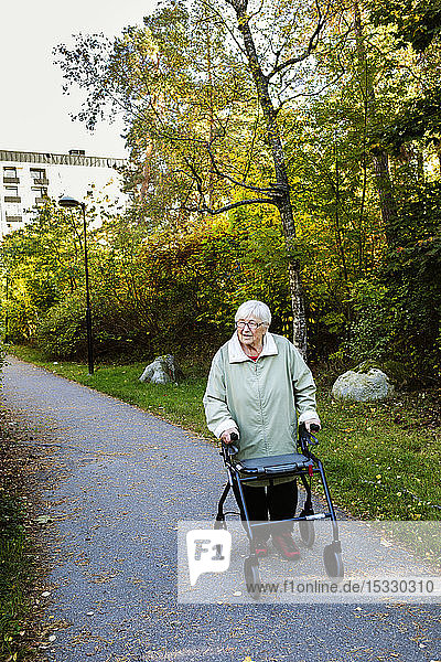 Senior woman using walking frame walking in park