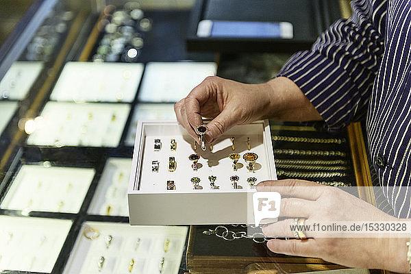 Hands of goldsmith examining box of rings