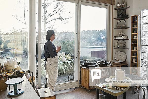 Woman by window in pottery workshop