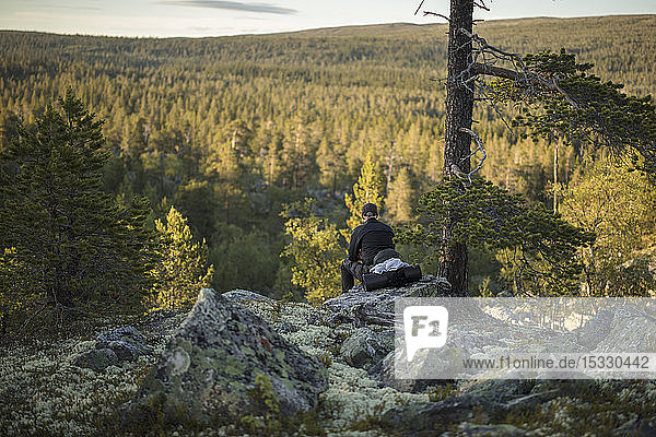 Man sitting on rock in Tofsingdalen Nature Reserve in Sweden