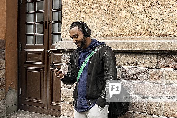 Junger Mann beim Musikhören im Freien