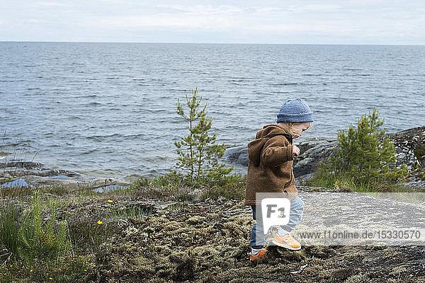 Girl walking on rocks by lake Girl walking on rocks by lake