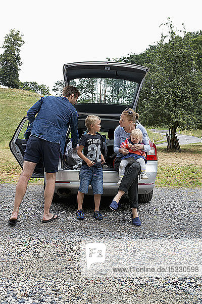 Family standing next to car
