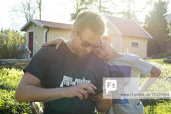 Father and son with smart phone