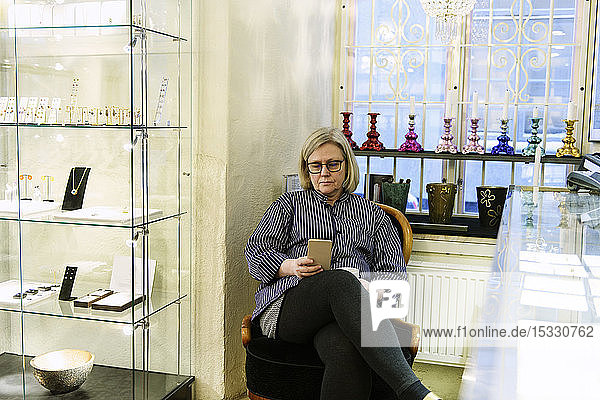 Goldsmith using smart phone in her jewellery store Goldsmith using smart phone in her jewellery store