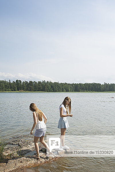 Girl and young woman standing on rocks near sea Girl and young woman standing on rocks near sea