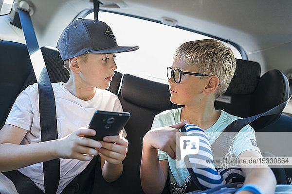 Boys with smart phone in car