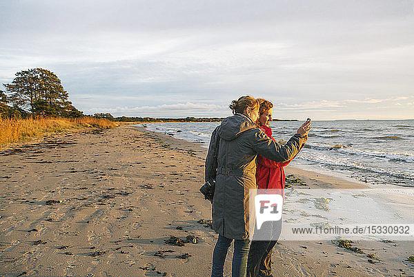 Women using smart phone on beach