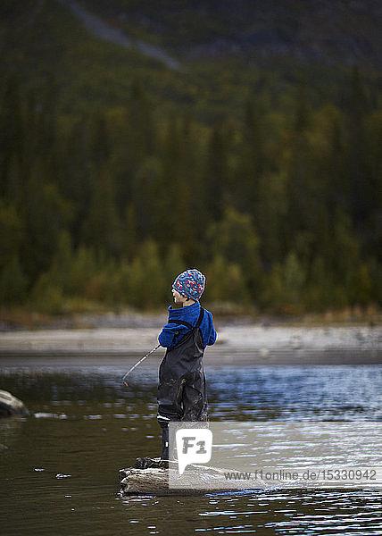 Boy fishing in river Boy fishing in river