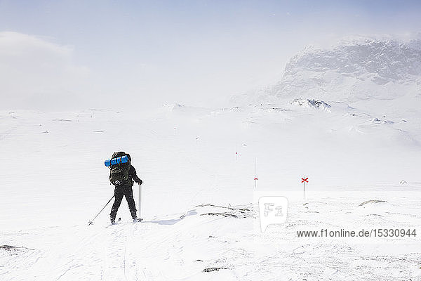 Woman skiing by mountains on Kungsleden train in Lapland  Sweden