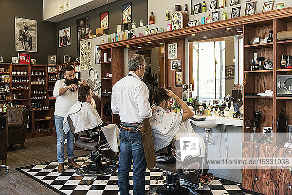 Barbers cutting customer´s hair
