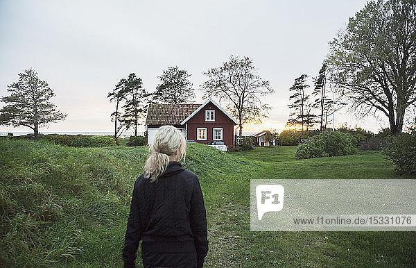 Frau im Feld beim Haus