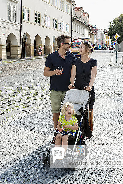 Couple with their daughter on a street