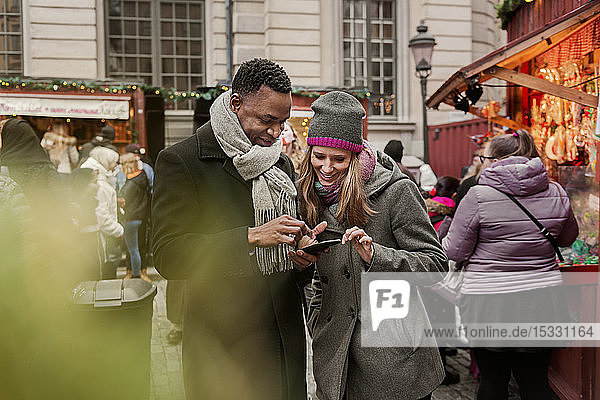Couple looking at cell phone at Christmas Fair