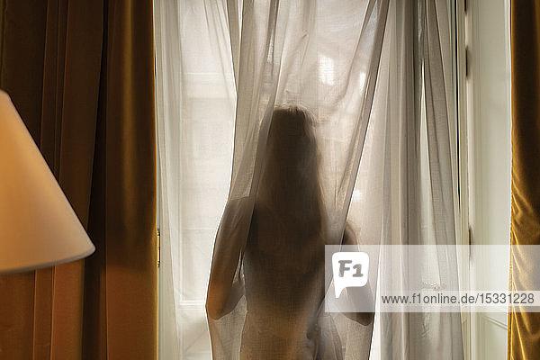 Silhouette eines Teenagers hinter einem Vorhang