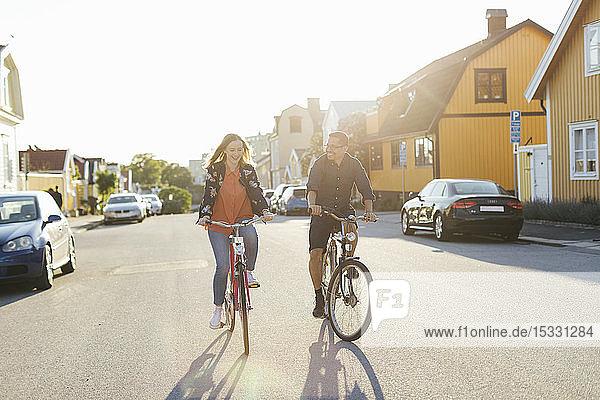 Couple cycling on suburban street Couple cycling on suburban street