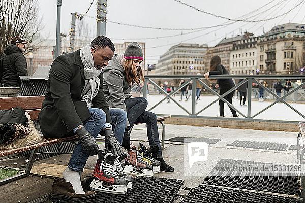 Couple putting on ice skates
