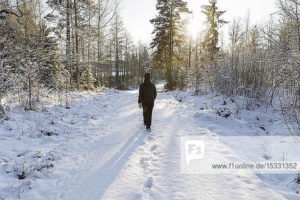 Ältere Frau geht auf verschneiter Straße