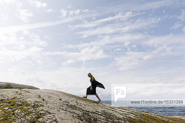 Woman wearing black walking on rock