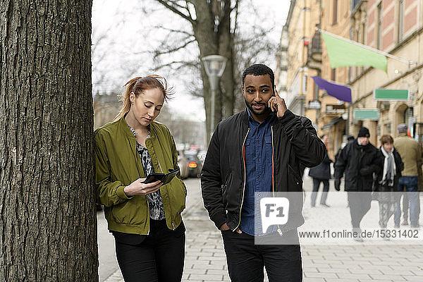 Couple using smartphones on sidewalk