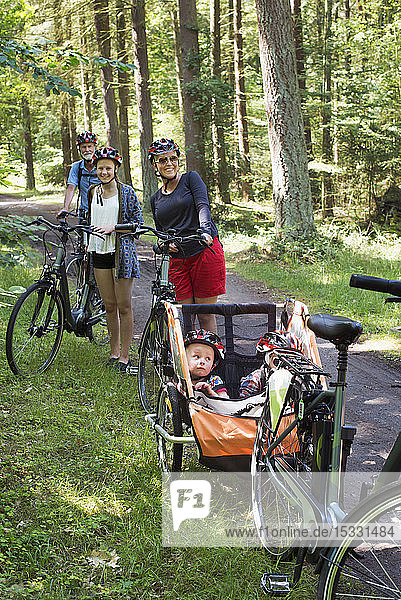 Family with bicycles in forest