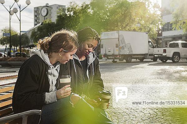 Teenager-Mädchen benutzen ihr Smartphone auf einer Bank
