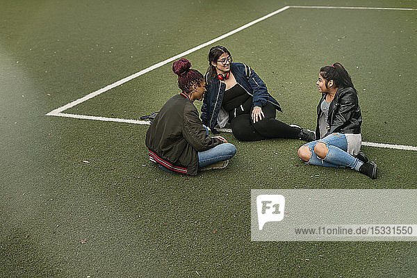 Teenager-Mädchen sitzen auf dem Tennisplatz