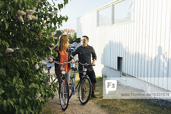 Couple pushing bicycles by house