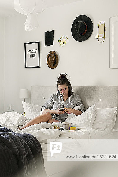 Young woman using smart phone in bed