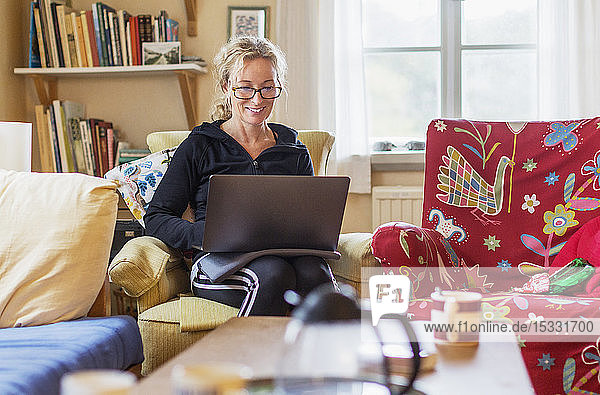 Woman using laptop on armchair