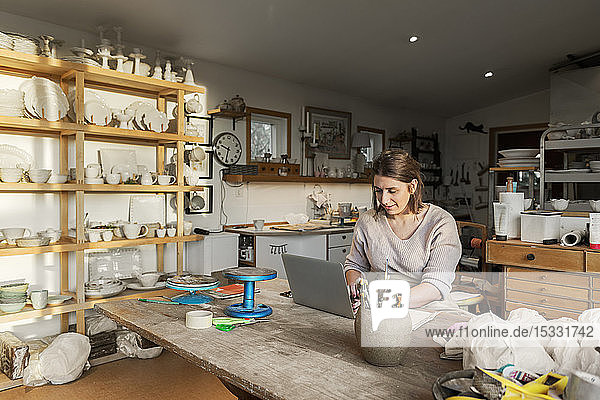 Woman using laptop in pottery workshop