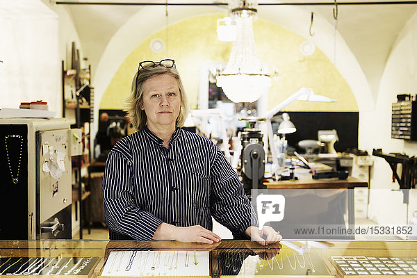 Portrait of goldsmith at counter of her jewellery store