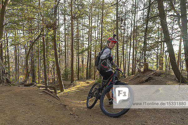 Mid adult man leaning on mountain bike in a forest