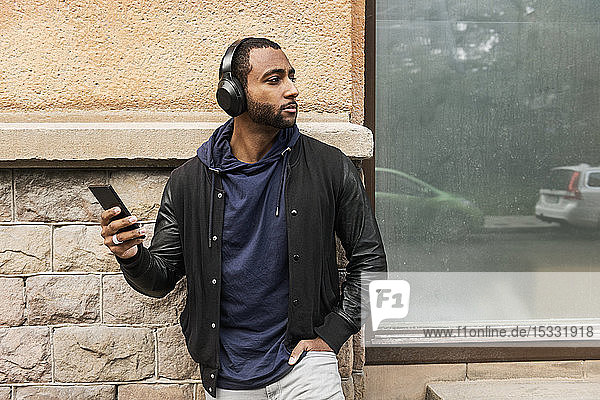 Young man listening to music outdoors