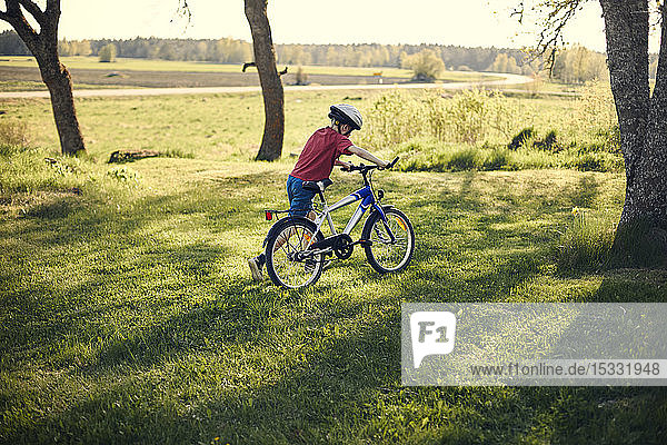 Boy pushing bicycle in on lawn