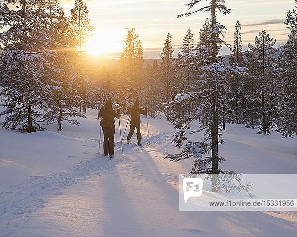 Menschen beim Skifahren bei Sonnenuntergang