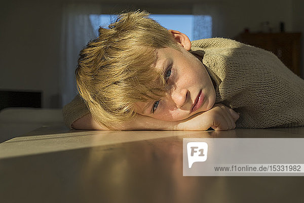 Boy leaning on table