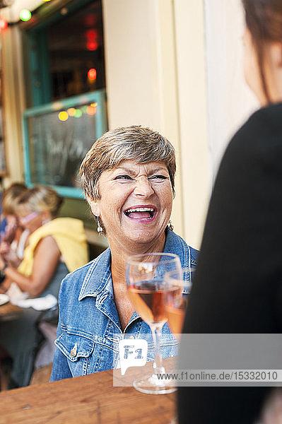Senior woman laughing in bar