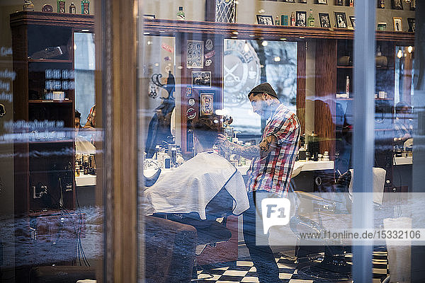 View through window of barber cutting customer´s hair