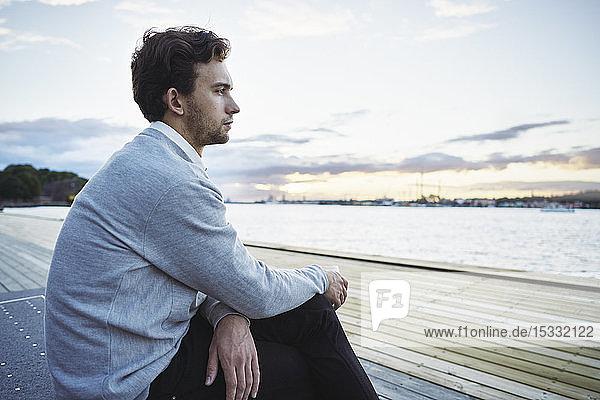 Junger Mann sitzt am Meer