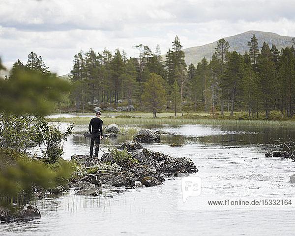 Man standing by river Man standing by river