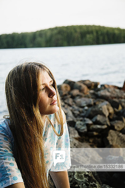 Portrait of young woman with lake in background