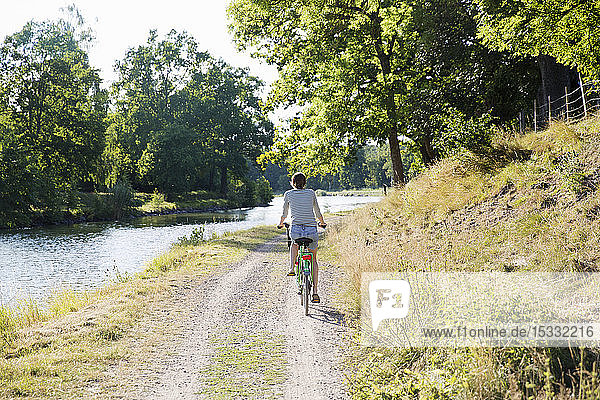 Woman cycling by canal