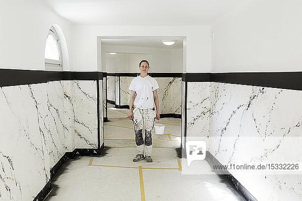 Maler im Hausflur eines Mehrfamilienhauses stehend