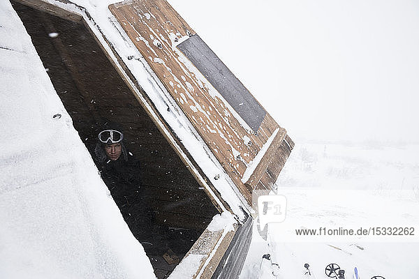 Man in roof of log cabin with snow