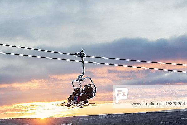 Silhouette of people on ski lift Silhouette of people on ski lift