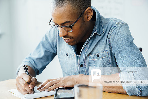 Man wearing glasses writing on note pad