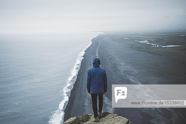 Man wearing blue coat above beach in Vik  Iceland